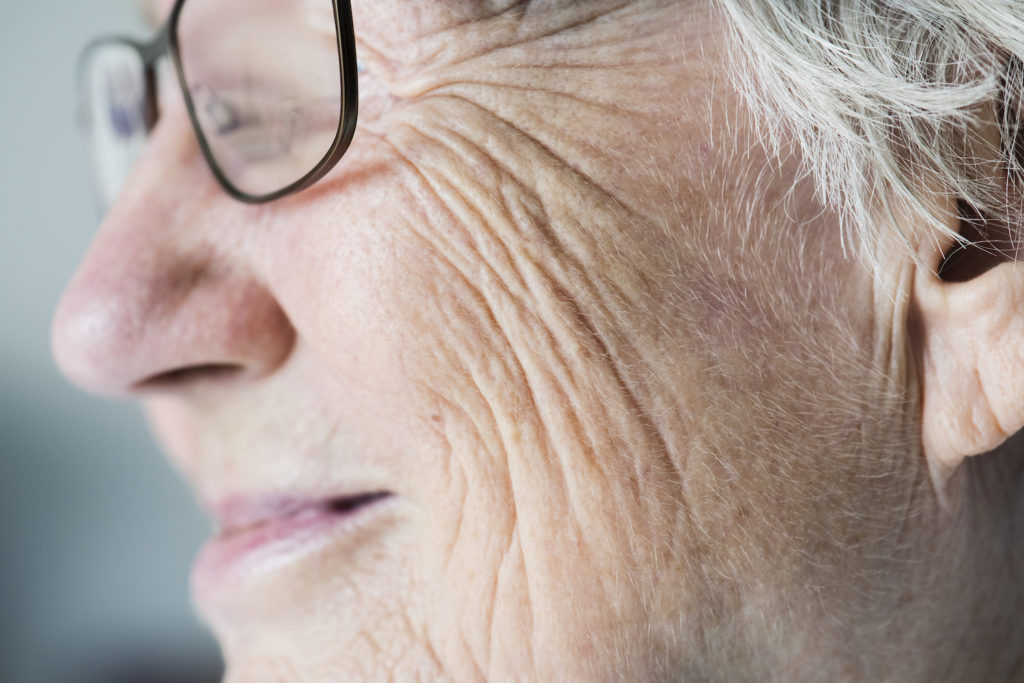Side closeup portrait of white elderly woman